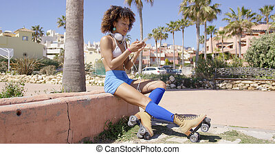 Female wearing rollerskates sitting on curb - Female wearing...