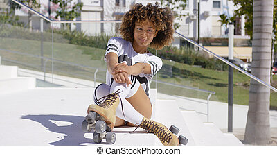 Smiling female sitting on stairs wearing rollerskates -...