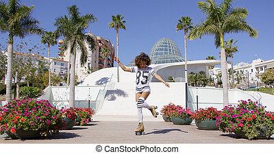 Female wearing rollerskates riding in park - Female wearing...