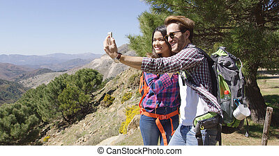 People taking selfie while hiking - Young couple hiking in...