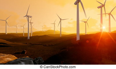 Wind turbine farm over green meadow, rays of light at sunset, tilt