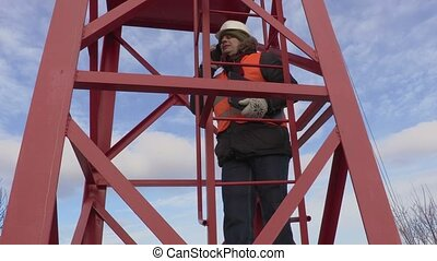 Engineer talking on phone and start to climb the tower