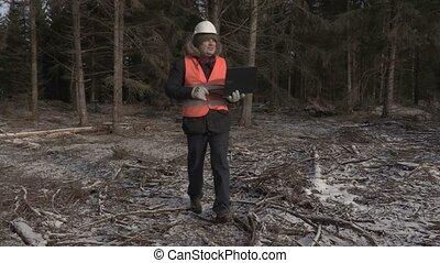 Lumberjack finish using laptop and walking away