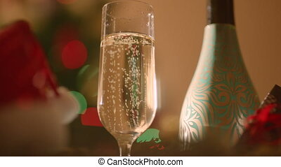 Glass filled with champagne and bottle of champagne on New...