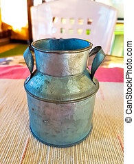 Old aluminum milk jug above on the table