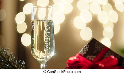 Glass filled with champagne and bokeh lights on the...