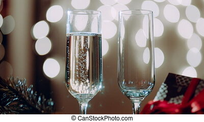 Two glasses filling with champagne and bokeh lights on the...