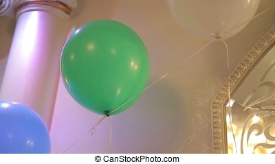 Green baloon on the ceiling .Childrens party balloon. Festive green baloon at the party. Baloon