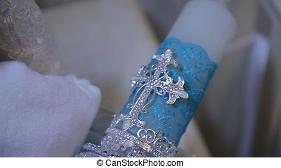 Decorative blue candle. White big decorative candle with holy cross. The figure of the cross on the candle. Selective focus