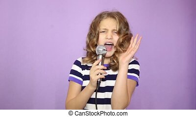 young girl with curly hair holding microphone, singing and...