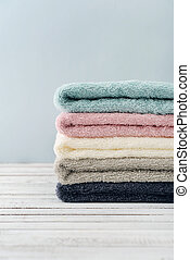 Stack of bath towels on light wooden background closeup