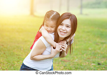 Mother and daughter in nature. - Pretty Asian woman...