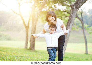 Mother and son playing outdoor.