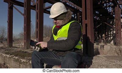 Worker sitting and using tablet near metal tanks