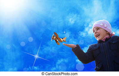 Kid  with toy wooden airplane against blue autumn sky background. Happy child playing outdoors