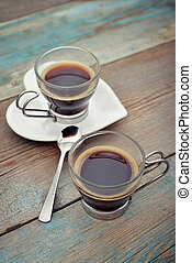 Two glass cups of coffee on wooden background