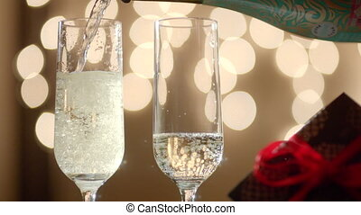 Two glasses filling with champagne and gift box with red...
