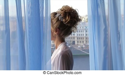 Beautiful bride in front of a window. Bride looking through the window. Bride near the window. Happy Bride looking in window. Blond or Brunette bride smiles while adjusting her earrings before the window. frail woman standing near a large window. Bride before ceremony. Wedding