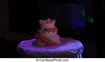 A multi level white wedding cake on a silver base and pink...