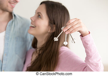 Real estate ownership concept, couple with keys to new home...