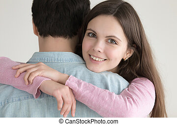 Portrait of young happy smiling woman hugging man with love...