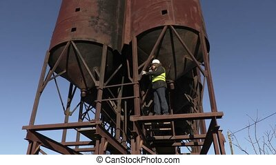 Worker talking on phone on metal tanks