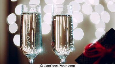 Two glasses filled with champagne and bokeh lights on the background