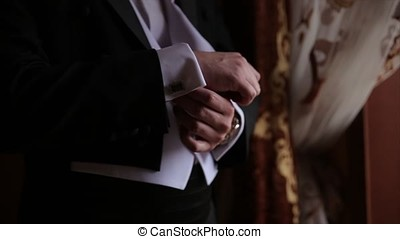 Groom is holding hands on the tie, wedding suit. close up of a hand man how wears white shirt and cufflink. Business man fixing black tie on white shirt. Groom on wedding day fixing tie, vintage effect. Closeup of a man in black suit correcting a sleeve. groom wear cufflink close up shot with sea view. Wedding