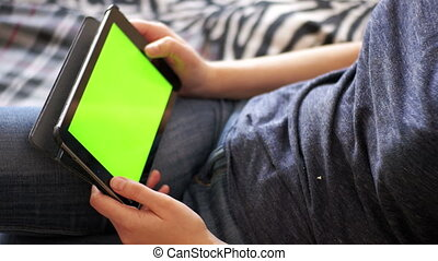 Young Woman Lying on Bed and using Tablet with Green Screen...