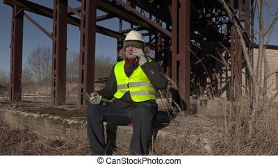 Worker sitting and talking on phone near metal tanks