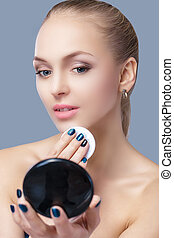 beautiful blond woman holding cosmetic sponge and looking in...