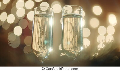 Two glasses filled with champagne and bokeh lights - Two...