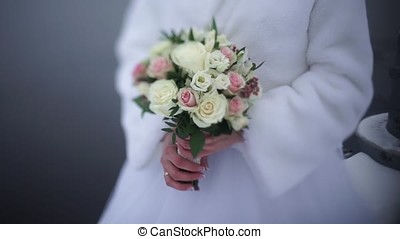 bride with flowers in hand outdoors. The bride is nervous before the wedding. Bride holding a perfume. nice wedding bouquet in bride's hand. Bride is holding beautiful bright wedding bouquet. the bride holding wedding bouquet of pink and white roses. Woman