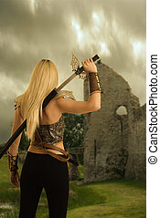 back of woman warrior drawing her sword with castle in...