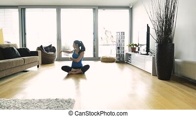 Young woman exercising at home, stretching legs and arms. -...