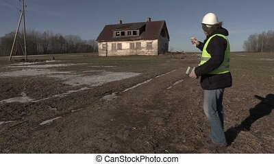 Construction contractor counting money near abandoned house