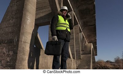Engineer checking the bridge and talking on phone