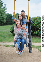 Happy young cheerful family of four at playground's swings -...