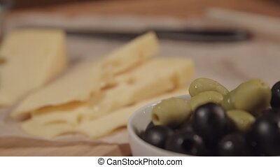 a woman takes an olive from the plate.