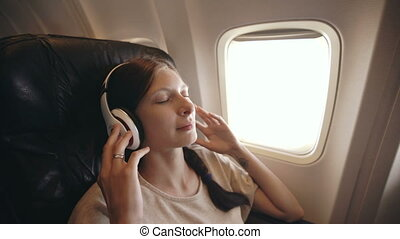 Young woman in wireless headphones listening to music and smiling during fly in airplane