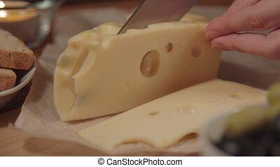 a woman cuts the cheese Maasdam.