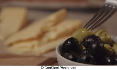 a fork takes an olive from the plate, next on the table is...