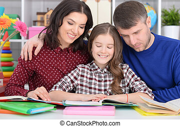Parents helping daughter with lessons