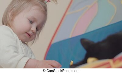 little girl plays with a cat at home