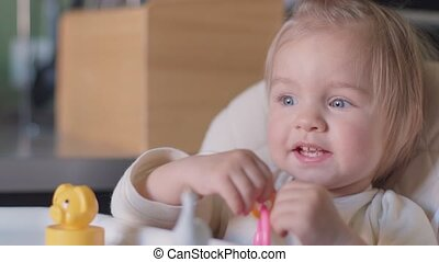 Cute little girl sitting at table playing with toy and...