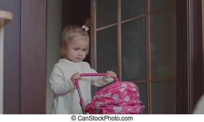 little girl plays a toy pram in the house.