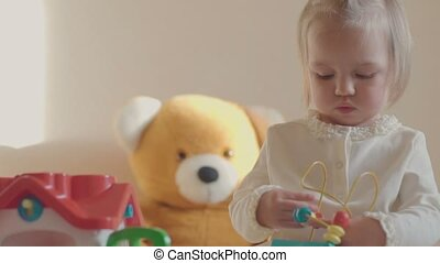 little girl in a room with toys.