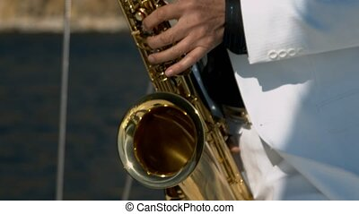 Musician is playing on saxophone in open sea. Close-up on...