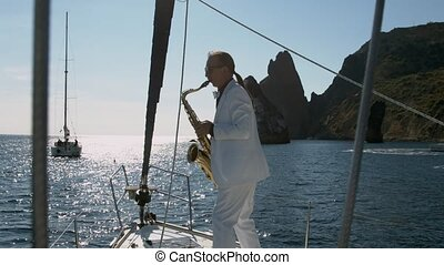 Saxophonist performs jazz on saxophone at white yacht in...