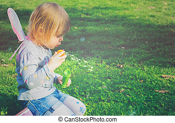 Toddler girl with butterfly wings having fun in the park, blowing soap bubbles